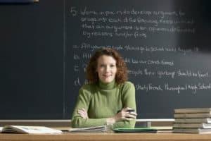 Nauczycielka angielskiego na tle tablicy