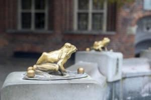 złote żaby na pomniku Flisaka