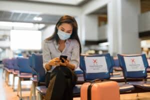 turystka z walizką z maseczkę na twarzy