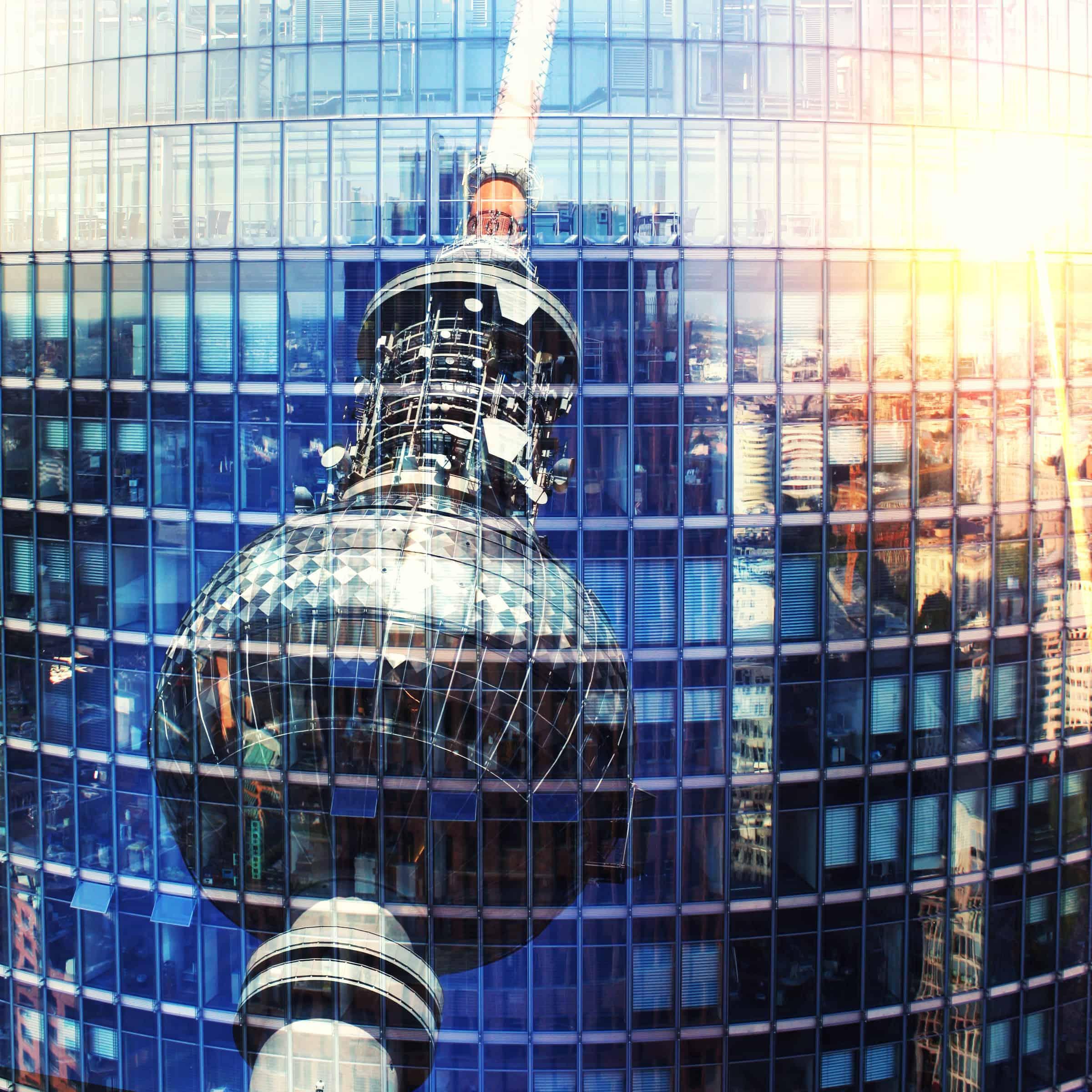 odbicie wieży telewizyjnej na ścianie wieżowca