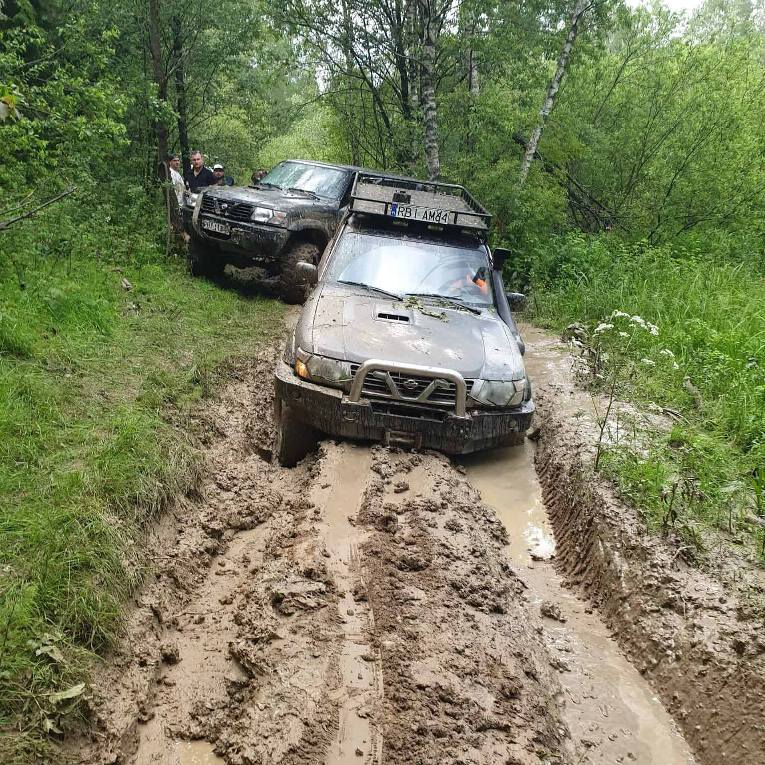 samochody terenowe na błotnistej drodze leśnej