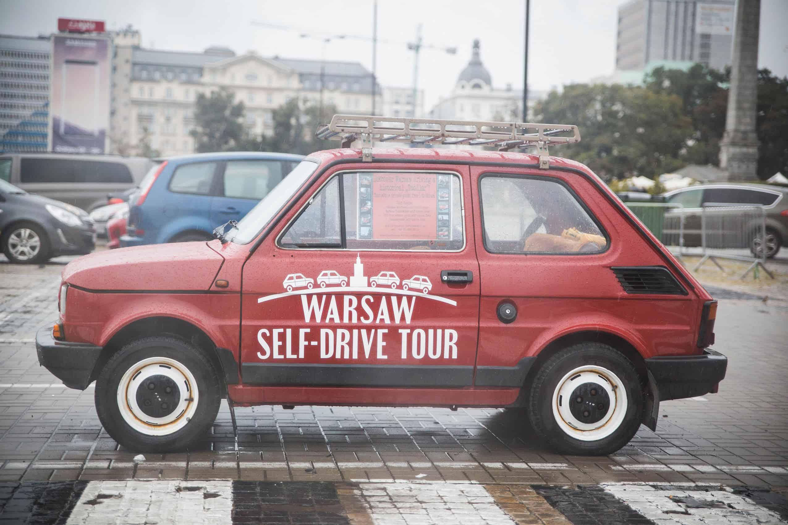 czerwony maluch, którym można pojeździć po Warszawie