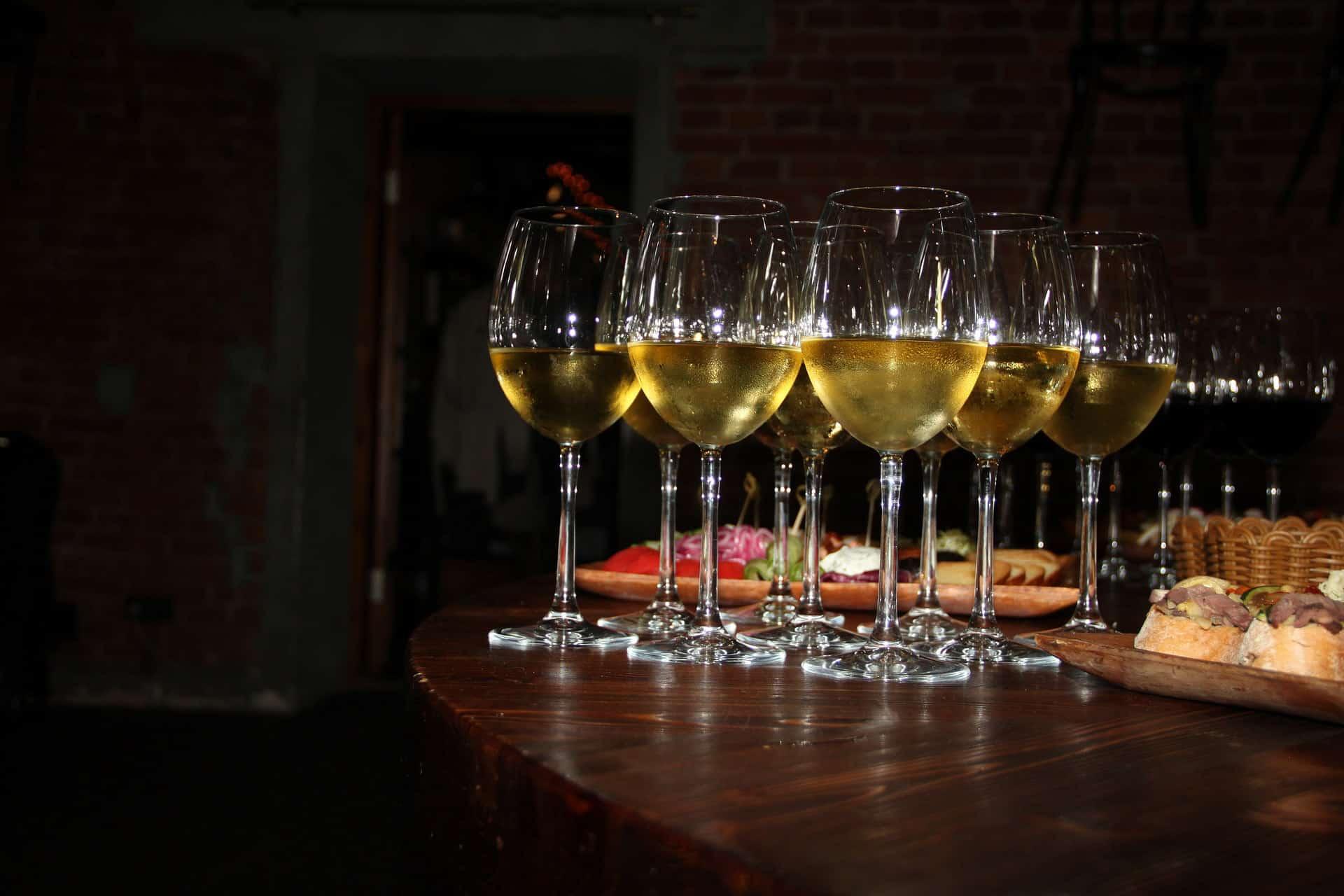 kieliszki białego wina na stole z zakąskami