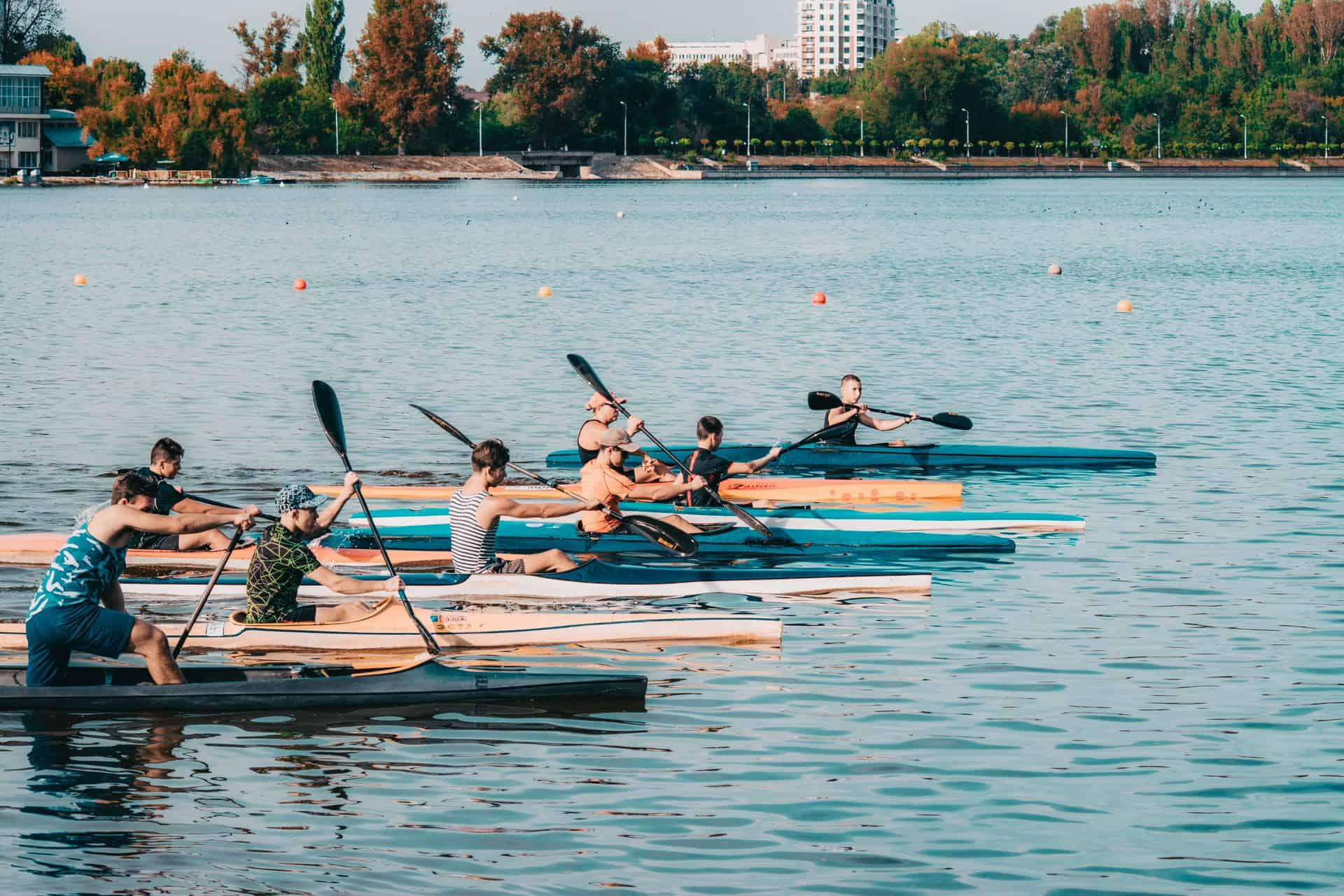 grupa kajakarzy płynąca wzdłuż parku