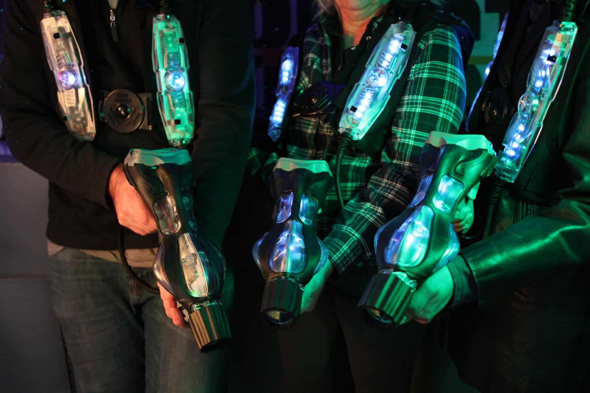 grupa osób w podświetlonych kamizelkach z pistoletami do laser tag