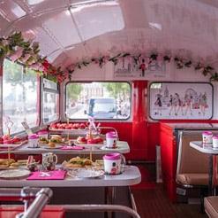 wnętrze londyńskiego autobusu z podwieczorkiem na stołach