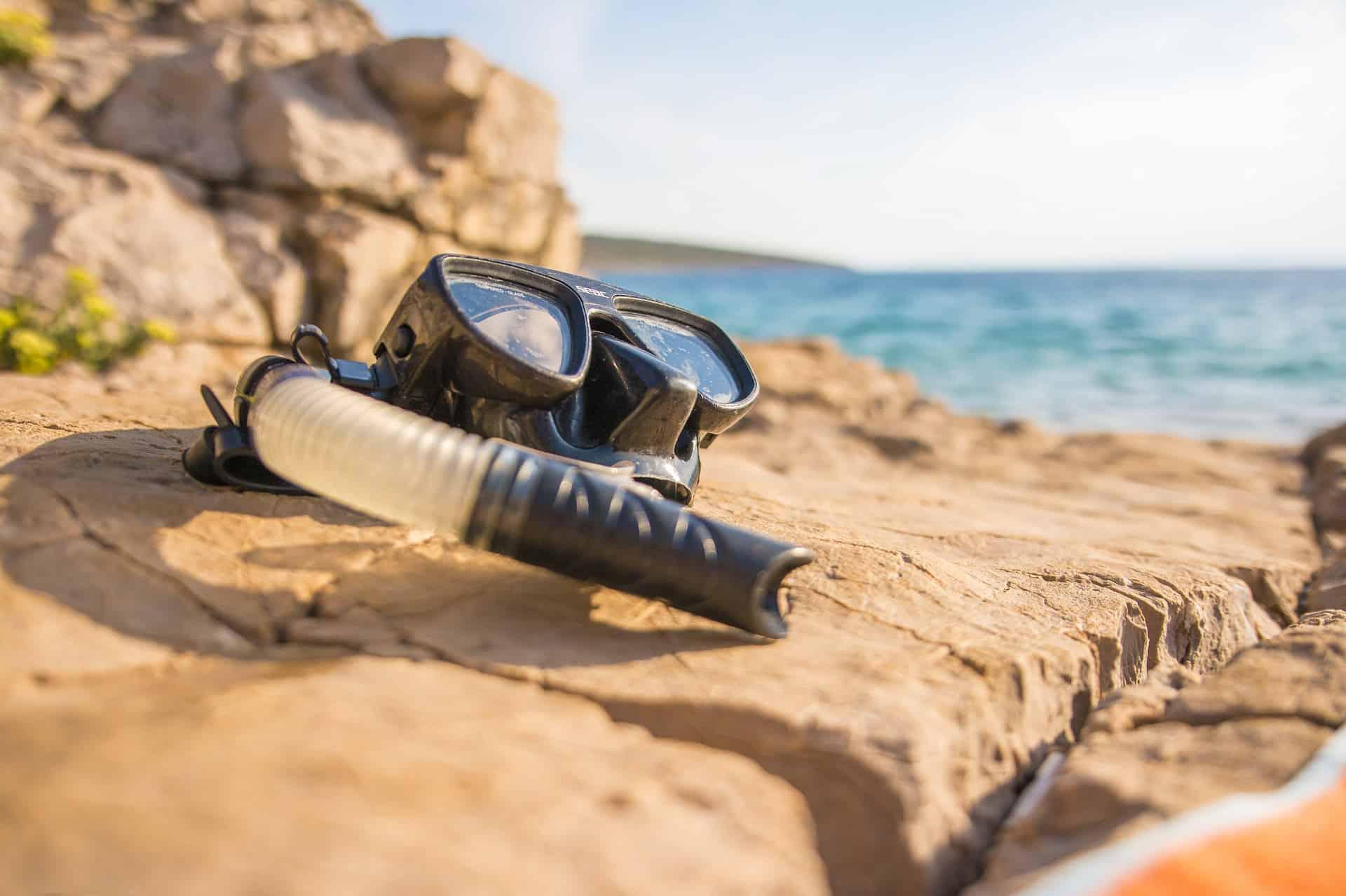 akcesoria do snorkelingu leżące na skale na brzegu morza
