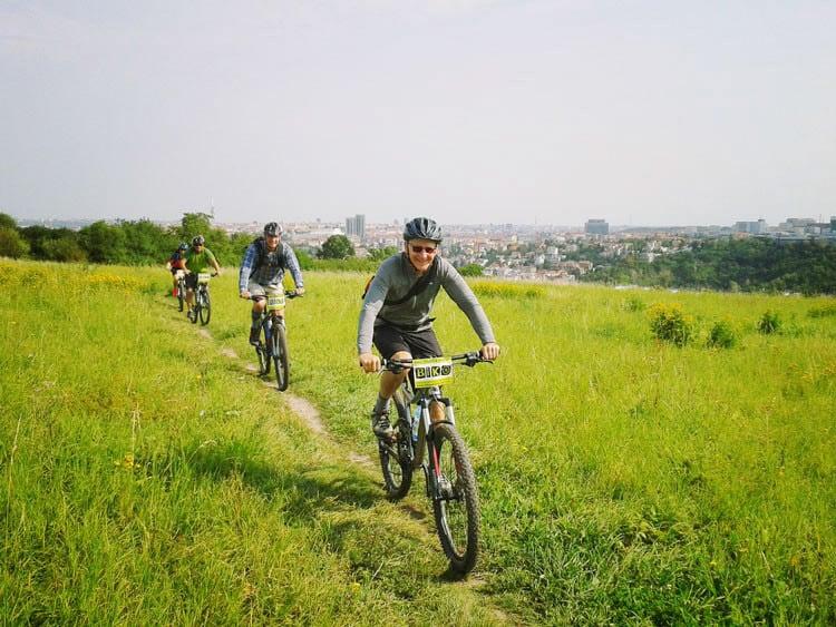 czwórka rowerzystów na wzgórzu z widokiem na Pragę