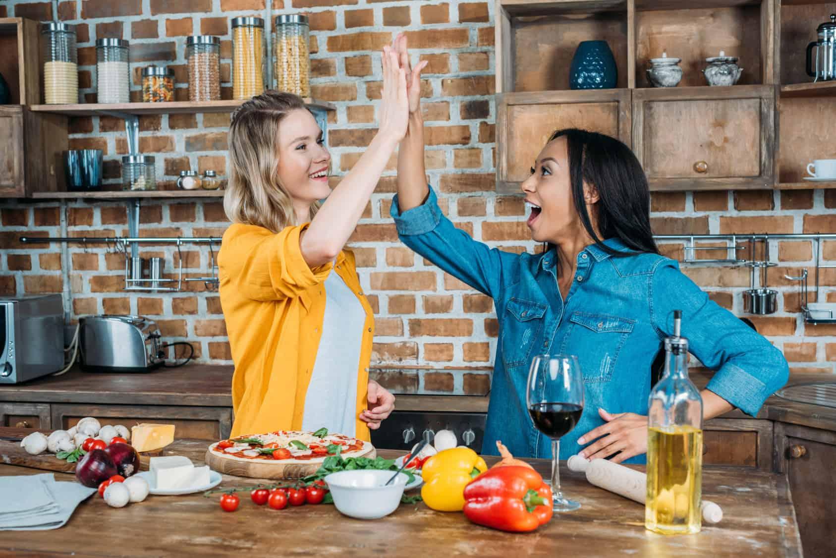 dwie młode kobiety przygotowujące pizzę