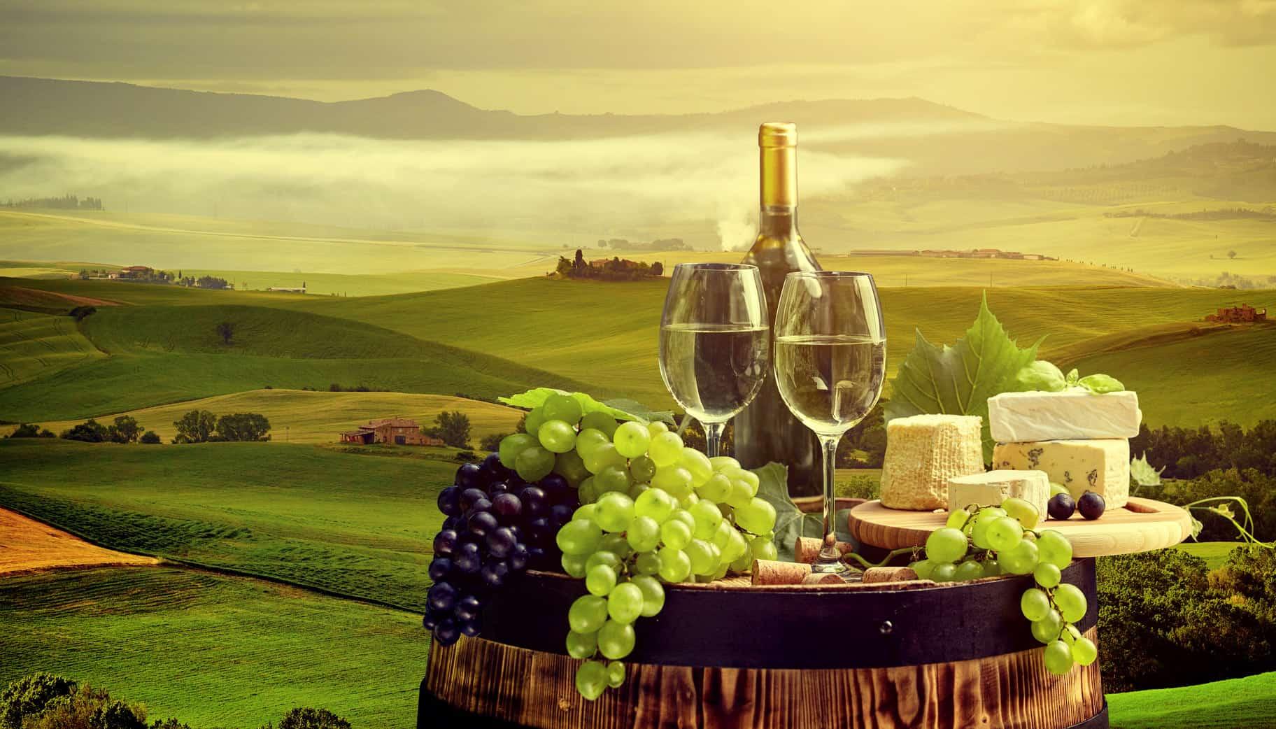 toskańskie wino, owoce i sery z krajobrazem w tle