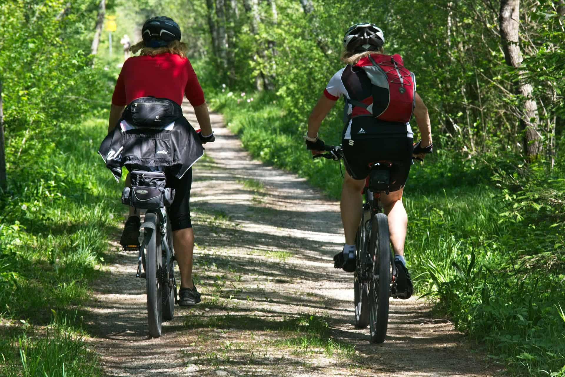 dwie rowerzystki jadące przez las