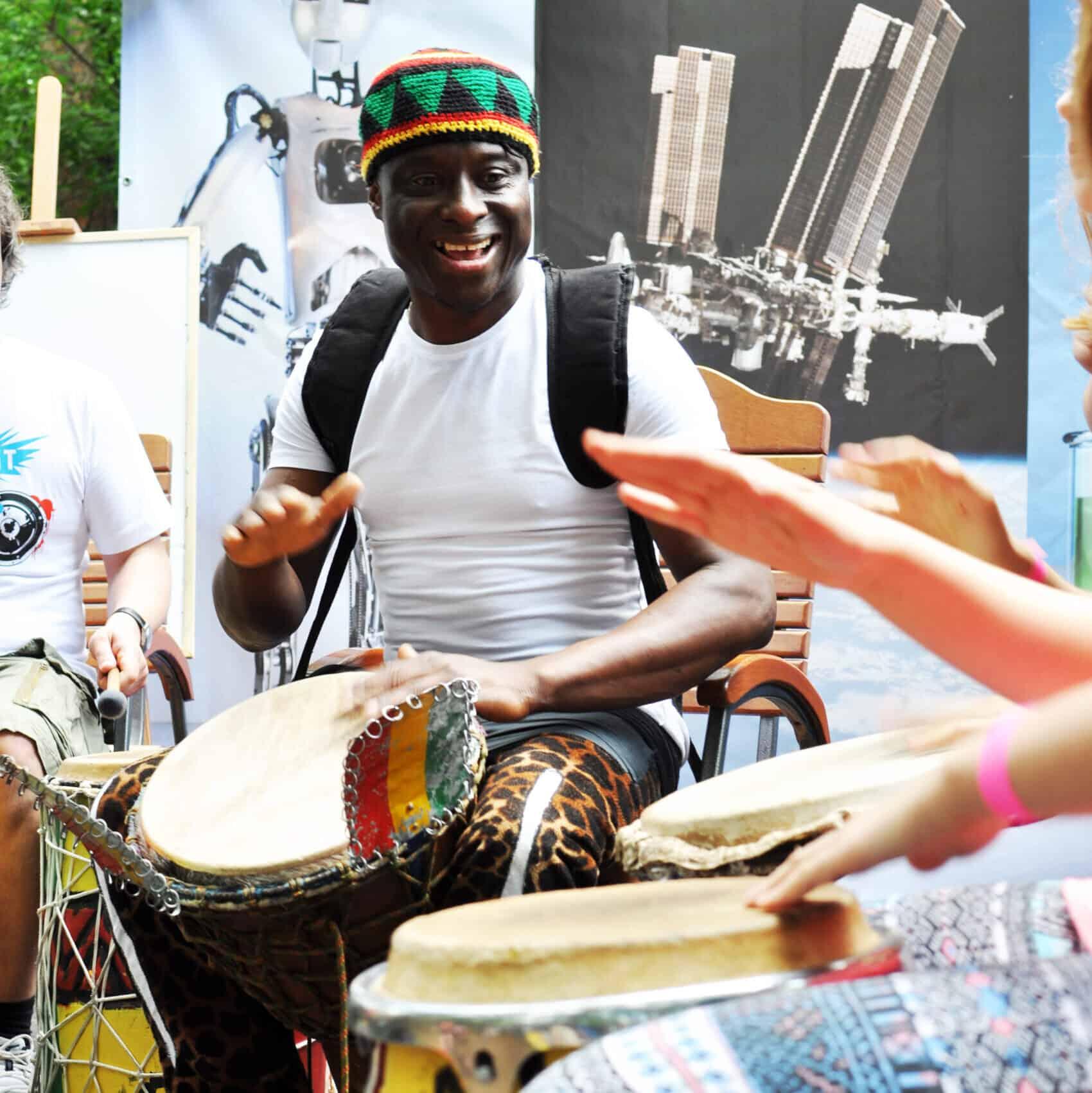 roześmiany mężczyzna grający na bębnie djembe