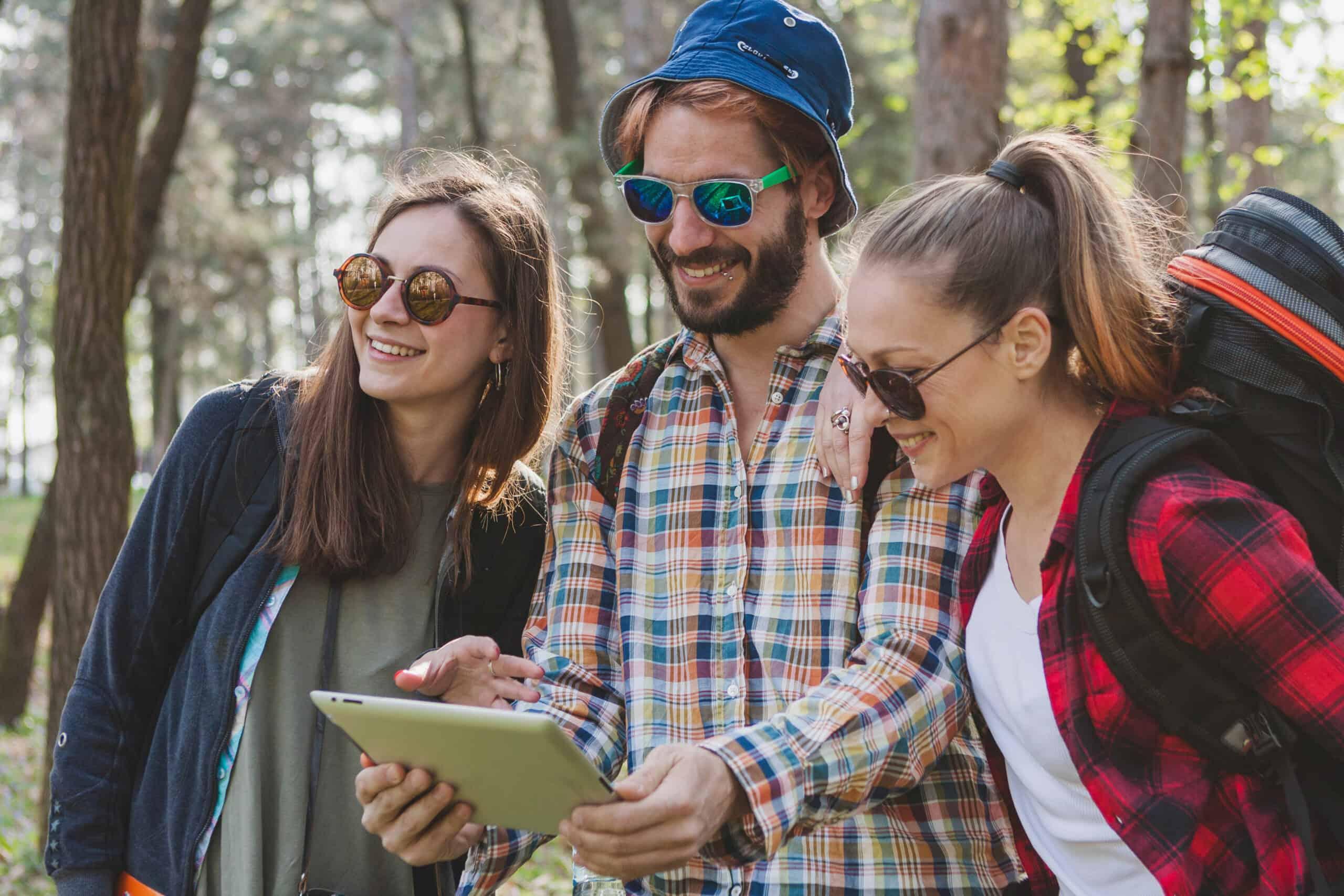 trójka turystów z plecakami w lesie