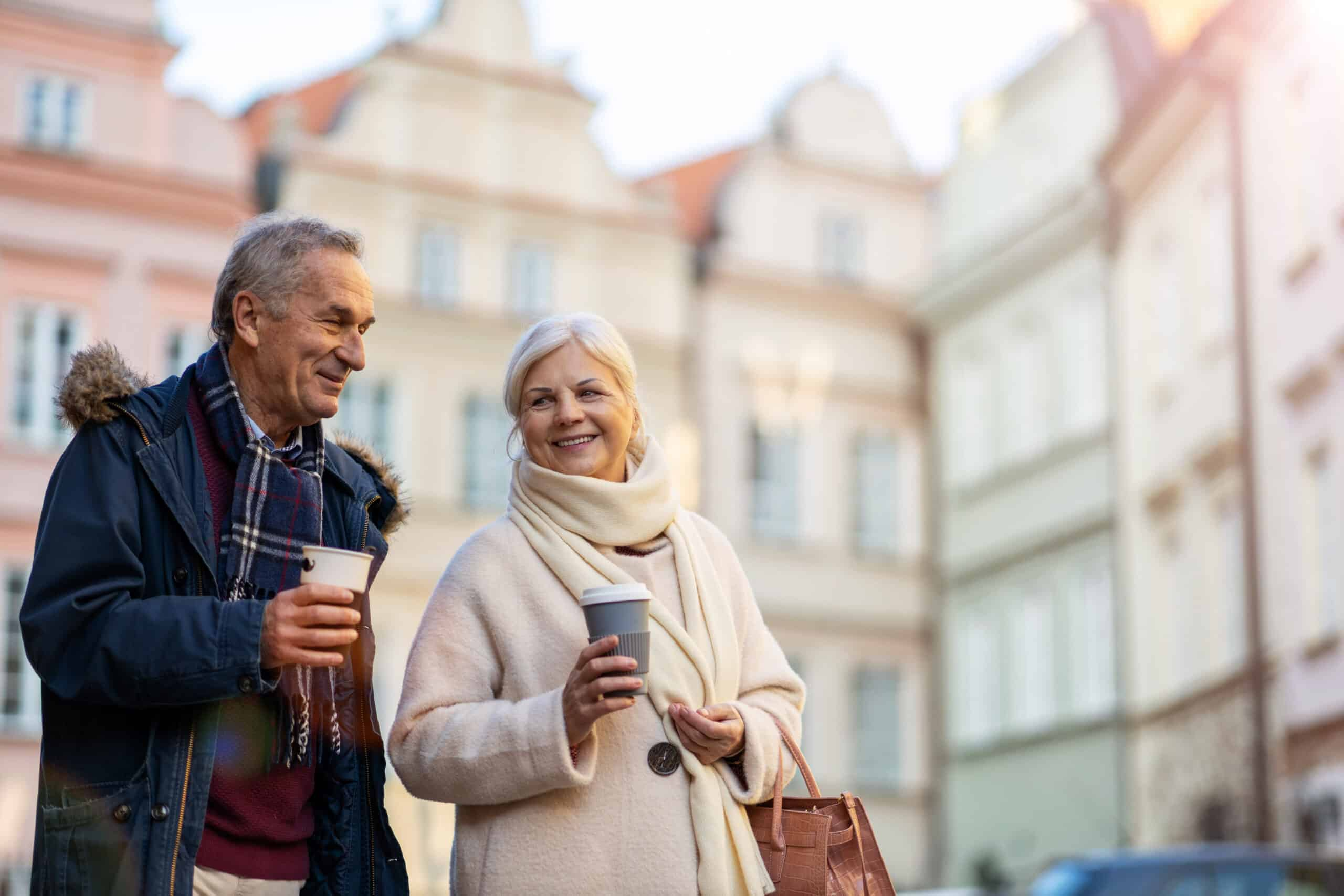 para seniorów spacerująca z kawą po starówce