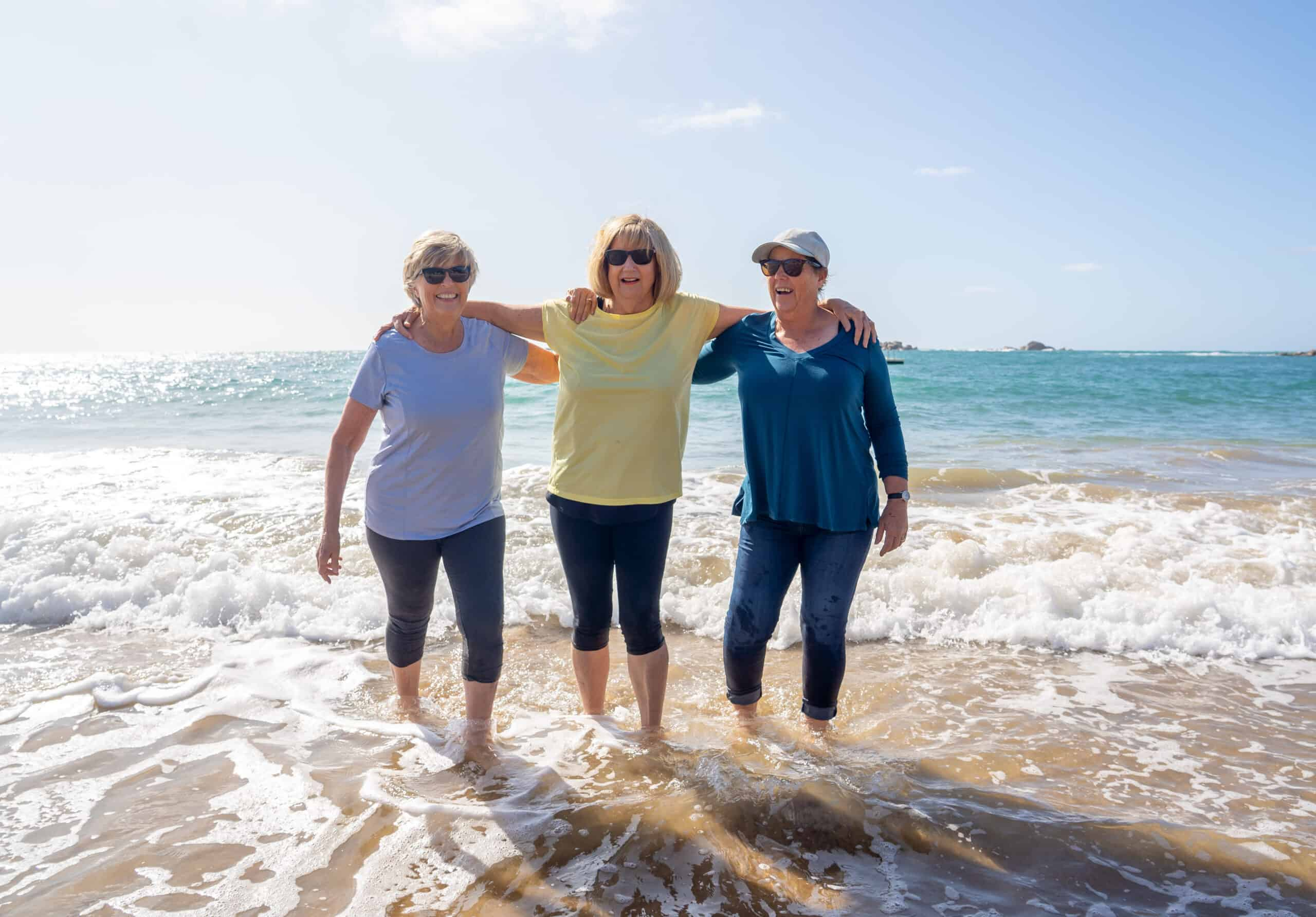 trzy seniorki stojące ze stopami zanurzonymi w morzu