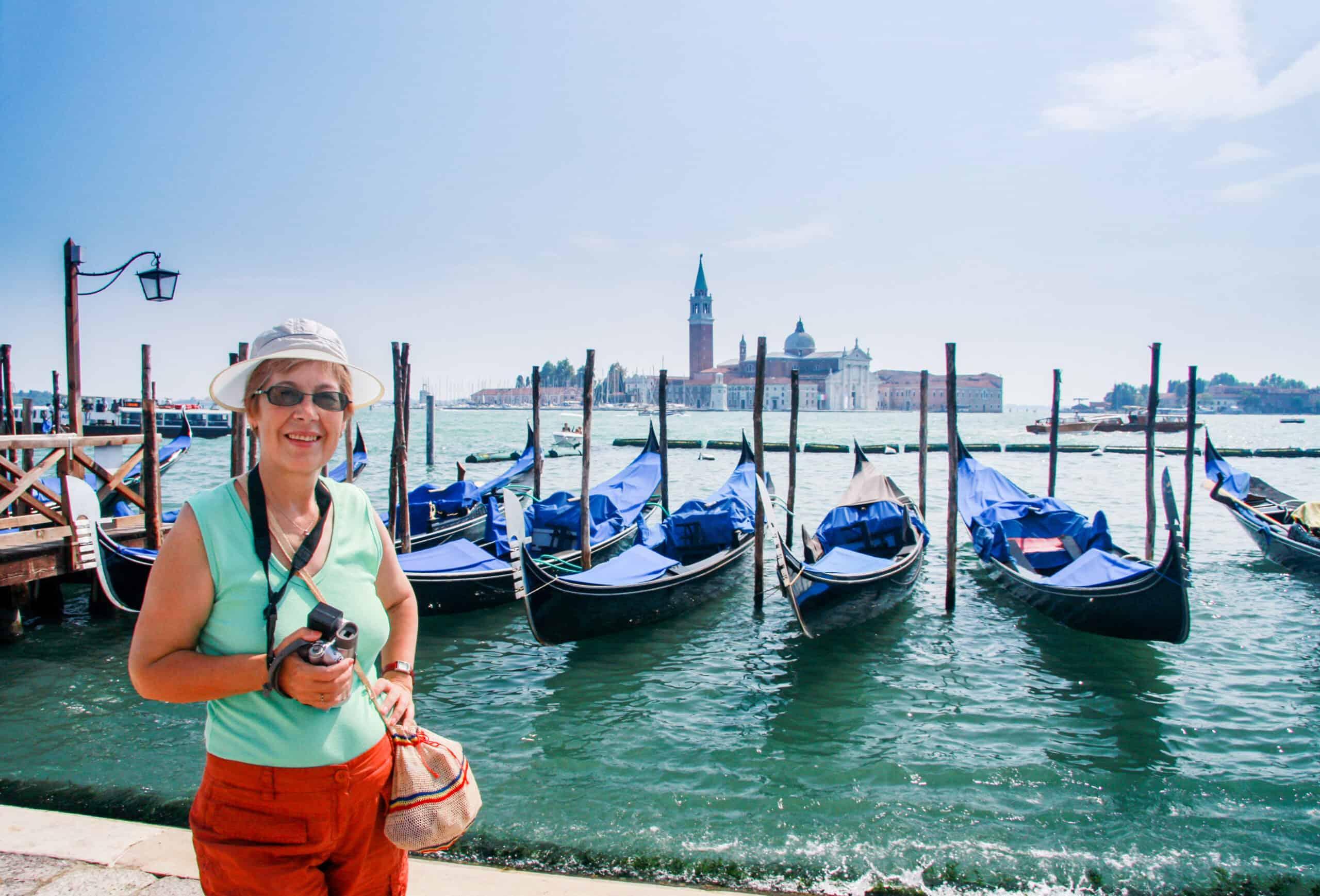 turystka w starszym wieku przy gondolach w Wenecji
